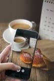 Fotografiando el café y el buñuelo calientes en el fondo de madera usado para f imagen de archivo