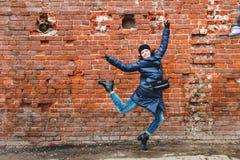 Fotografiaron a la muchacha sonriente en un salto en un fondo de la pared de ladrillo imagenes de archivo