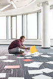 Fotografie d'organizzazione dell'uomo d'affari mentre sedendosi sul pavimento all'ufficio creativo Immagini Stock