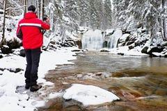 Fotografie in der roten Jacke mit Digitalkamera in den Händen macht Foto des Winterwasserfalls Lizenzfreie Stockfotografie