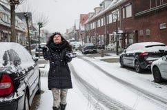 Fotografie einer Frau, die mit Schnee auf einer Straße in Holland spielt lizenzfreies stockbild