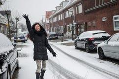 Fotografie einer Frau, die mit Schnee auf einer Straße in Holland spielt stockfotografie