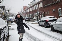 Fotografie einer Frau, die mit Schnee auf einer Straße in Holland spielt lizenzfreie stockbilder