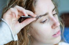 Fotografie eines Mädchens, das ihre Augenbrauen mit Pinzette zupft stockbilder