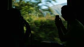 Fotografie turistiche dell'uomo su uno smartphone un paesaggio della montagna dalla finestra del treno, viaggiante dalla ferrovia stock footage