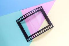 FotografieBilderrahmen in Form des Weinlesefotofilm-Streifennegativs auf minimalistic Konzept des mehrfarbigen Hintergrundes Stockfotografie