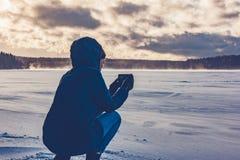 Fotografier för en flicka på telefonen en djupfryst sjö fotografering för bildbyråer