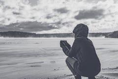 Fotografier för en flicka på telefonen en djupfryst sjö arkivfoton