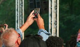 Fotografieren mit einem intelligenten Telefon an einem Musikereignis Stockfoto
