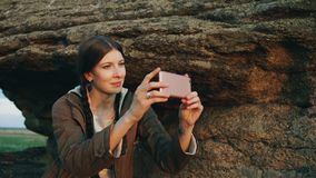 Fotografierende Landschaft des jungen touristischen Frauenwanderers auf ihrer Smartphonekamera nachdem dem Wandern auf Felsen bei Stockbilder