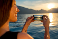 Fotografierender Sonnenuntergang der Frau Stockfotos