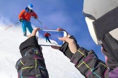 Fotografierte Skifahrer mit Handy Stockfoto