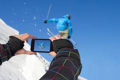 Fotografierte Skifahrer springen mit Handy Stockbilder