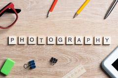 Fotografiewort von Blöcken und von Büromaterial auf Geschäftsarbeitsplatz Lizenzfreie Stockfotografie