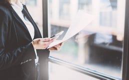 Fotografii biznesowa kobieta jest ubranym kostium, wzruszającego smartphone ekran i mienie dokumenty w rękach, Otwartej przestrze Obrazy Royalty Free