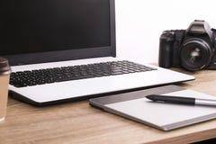 Fotografii blogger, fotograf, ja/specjalisty ` s powierzchni biurowa typowy stół z laptopem, pustym ekranem, filiżanką i elektron zdjęcie royalty free