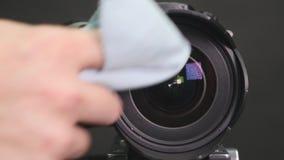 Fotografii ręki cleaning kamery obiektyw z spcial miękkim małym płótnem Poruszający płótno w kółkowych ruchach Filmujący w wolnym zbiory