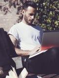 Fotografii studenckiego siedzącego miasta parkowa ławka i texting wiadomość notatnik Używać bezprzewodowego internet Studiować pr Obraz Stock