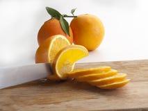 Fotografisch stilleven van sommige sinaasappelen en gesneden besnoeiingen †‹â€ ‹op een scherpe raad 2 stock afbeelding