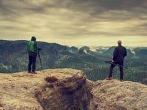 Fotografkontrollskärm av kameran på tripoden Manstag på klippan royaltyfri fotografi