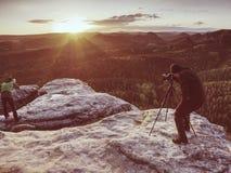 Fotografkontrollsk?rm av kameran p? tripoden Manstag p? klippan fotografering för bildbyråer
