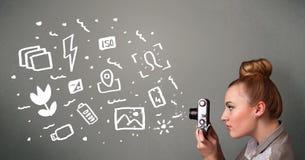 Fotografmädchen, das weiße Fotografieikonen und -symbole gefangennimmt Stockbild
