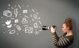 Fotografmädchen, das weiße Fotografieikonen und -symbole gefangennimmt Lizenzfreie Stockfotos