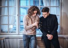 Fotografmann, der Fotos auf Digitalkamera zeigt, um gekleidetem und ernstem custumer zu entsprechen stockbilder