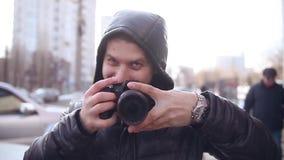 Fotografmann macht ein Foto eines Durchschnittsbürgers in einer Haube stock video footage