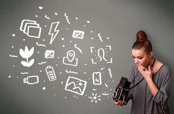 Fotografmädchen, das weiße Fotografieikonen und -symbole gefangennimmt Stockfoto