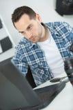 Fotografo che controlla le foto in camera allo scrittorio in ufficio fotografie stock libere da diritti