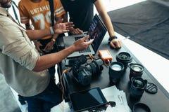 Fotografo che fa a dopo la rassegna del tiro con il gruppo fotografie stock libere da diritti