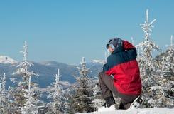 Fotografo che fotografa panorama di inverno in alte montagne Fotografia Stock