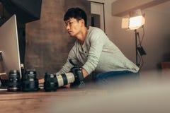 Fotografo che installa il suo computer per il tiro fotografia stock