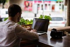 Fotografo che lavora ad un computer portatile Fotografie Stock