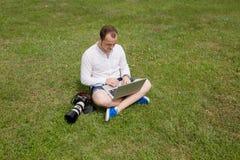 Fotografo che lavora ad un computer portatile all'aperto Fotografie Stock