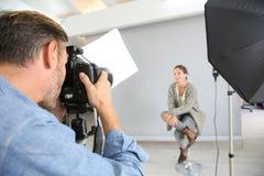 Fotografo che lavora nel modello della donna della fucilazione dello studio Fotografia Stock Libera da Diritti