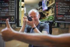 Fotografo che prende le foto delle vie vivaci con i ristoranti immagini stock