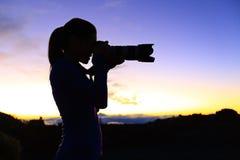 Fotografo che prende le immagini con la macchina fotografica di SLR Immagini Stock