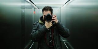 Fotografo che prende un selfie cinematografico dello specchio con lo sguardo analogico della pellicola per luce artificiale e gra fotografie stock libere da diritti