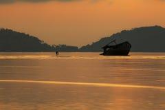 Fotografo che prende una foto della barca del relitto sulla spiaggia bassa del mare contro il bello cielo di aumento del sole immagini stock libere da diritti