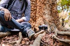 Fotografo che riposa sotto un grande albero con la macchina da presa Immagini Stock