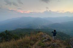 Fotografo che spara il bello paesaggio delle montagne di sera della Tailandia Immagini Stock