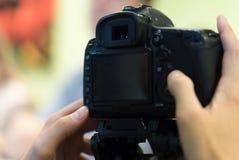 Fotografo con la macchina fotografica di DSLR immagine stock
