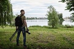 Fotografo con la macchina fotografica ed il treppiede immagine stock