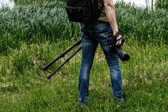 Fotografo con la macchina fotografica ed il treppiede fotografia stock