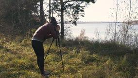 Fotografo con la macchina fotografica su un treppiede - artista femminile del paesaggio che prende le foto di viaggio in natura archivi video