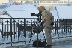 Fotografo con la macchina fotografica sul treppiede che prende il paesaggio urbano fotografie stock libere da diritti