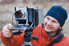 Fotografo con la vecchia fucilazione della macchina fotografica all'aperto. Fotografie Stock Libere da Diritti