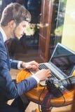 Fotografo del giovane che lavora al caffè, facendo uso del computer portatile immagine stock